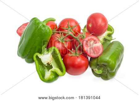 Branch with the ripe red tomatoes several green bell peppers and bisected one tomato and bisected one pepper on a light background