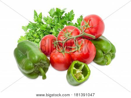 Branch with several ripe red tomatoes two whole and one half of the green bell peppers and bundle of the parsley closeup on a light background