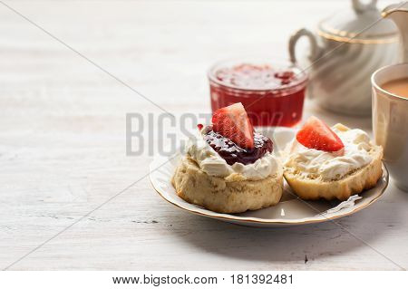 English tea with scones and clotted cream jam strawberries on the white table copy space for text selective focus