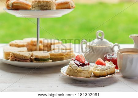 English afternoon teas in the garden cafe: scones with clotted cream and jam strawberries with various sadwiches on the background selective focus