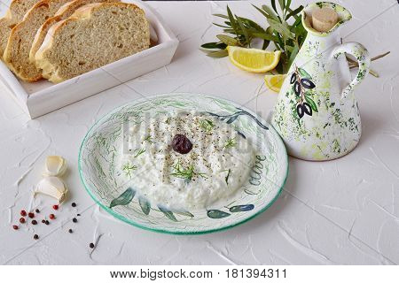 Homemade Greek traditional sauce tzatziki with cucumber garlic yogurt and lemon in a bowl and jar with olive oil on a abstract background. Healthy eating concept. Mediterranean lifestyle