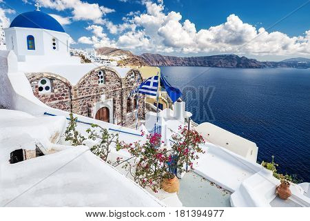 White architecture on Santorini island, Greece. Beautiful landscape with sea view, blue dome church and Greece flag.