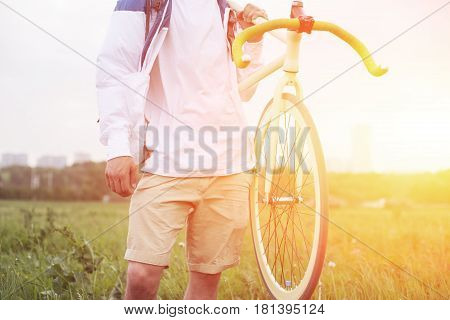 Man In Blank T-shirt Holding Bicycle In Green Field (intentional Sun Glare And Bright Color)