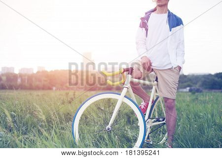 Young Man In Blank T-shirt Sitting On His Bicycle In The Field (intentional Sun Glare And Vintage Co