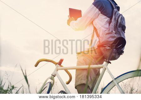 Young Man With Bicycle In The Green Field Taking Photo With Tablet Computer At Sunset (intentional S