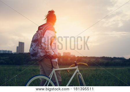 Young Man With Bicycle In The Green Field Looking Far Away At Sunset (intentional Sun Glare And Dark