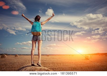 Happy And Young Girl With Outspread Hands And Backpack Greeting Sunset Outdoors (intentional Sun Gla