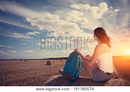 Young And Handsome Girl In White Shirt And Backpack Sitting On Haystack In The Field At Sunset (inte