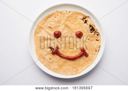 ketchup or fruit jelly/jam smile emoticon over indian bread / chapati / roti / paratha, indian kid's all time favourite breakfast or tiffin menu