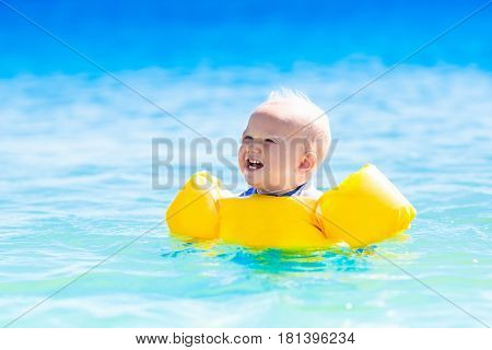 Baby Swimming In Ocean Water On Tropical Beach