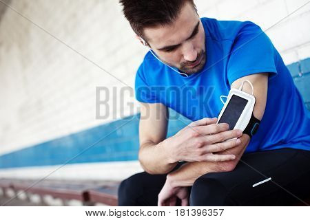 Male Athlete Touching Screen On Armband An Listening Music