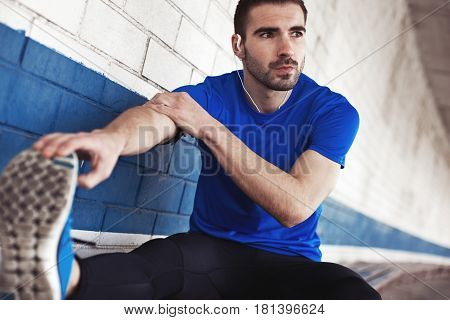 Young Male Athlete With Stubble And Earphones Doing Fitness Exercise