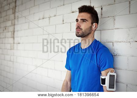 Portrait Of Handsome Athlete With Stubble, Earphones And Armband Standing Near Brick Wall