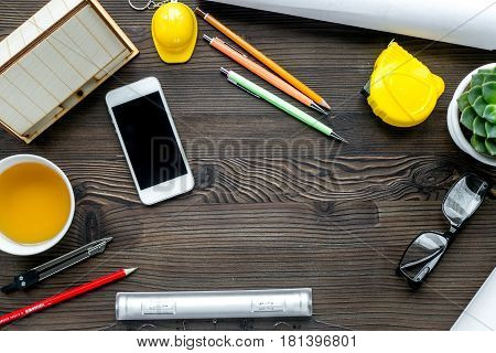 architect office with tools, cup and mobile in profession concept on wooden desk background top view