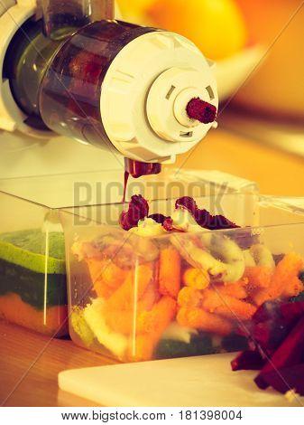 Making fresh vegetables juice in juicer machine close up. Healthy eating vegetarian food dieting concept