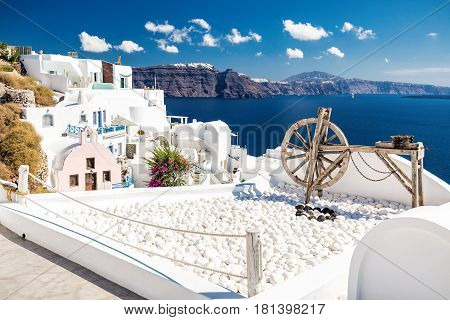 Beautiful wooden old tool as a decoration on a terace with white houses and blue sea and sky in Oia, the most beautiful village of Santorini island in Greece