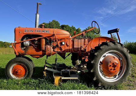 ALEXANDRIA, MINNESOTA, August 12, 2016: The restored orange tractor with a belly mower is an Allis Chalmers , a U.S. manufacturer of machinery for various industries including agricultural equipment, construction, power generation, and power transmission.