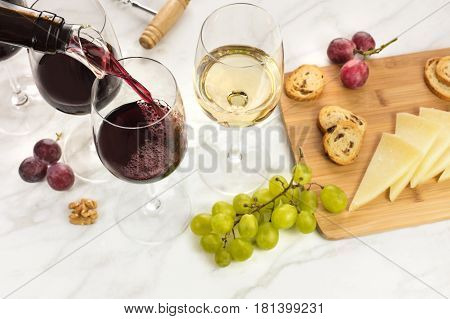 Red wine poured into a glass with dispenser at a tasting, with cheese, bread, and grapes. Selective focus