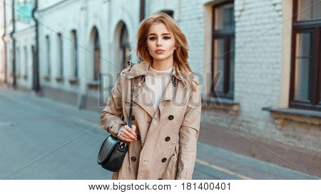 Beautiful Young Woman In A Stylish Light Coat With A Handbag On The Street