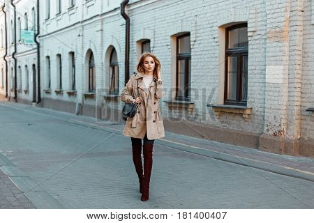 Beautiful Fashionable Young Girl In A Trendy Coat And Stylish Shoes With A Black Purse Walks In The