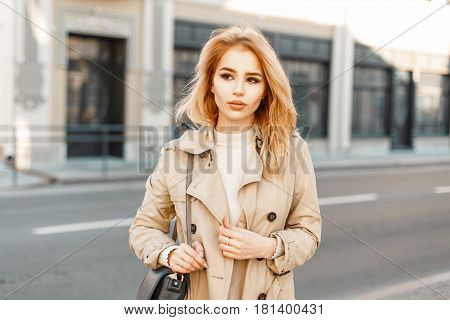 Beautiful Young Slender Girl In A Light Coat With A Bag On The Street
