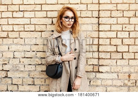 Beautiful Stylish Hipster Girl With Glasses In Coat And Handbag Near Vintage Brick Wall