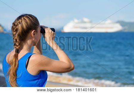 Young female tourist looking through binoculars at cruise ship (liner) and enjoying beautiful sea view. Woman wearing blue dress. Her hair braided in French plait. Outdoor portrait in summer.