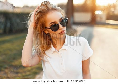 Beautiful Young Woman In Sunglasses And A White Polo Shirt Walking At Sunset