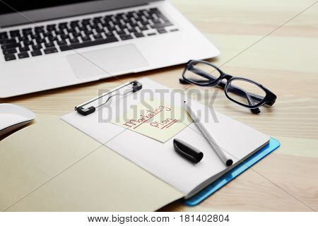 Notebook with text MARKETING PLAN on table