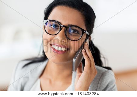 business, technology, communication and people concept - happy smiling businesswoman or secretary calling on smartphone at office