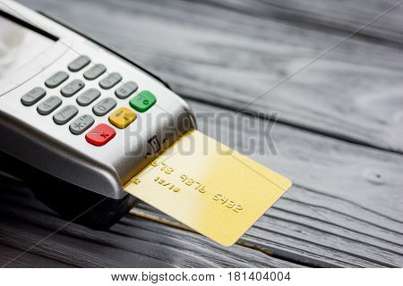 payment terminal with credit card on wooden table background