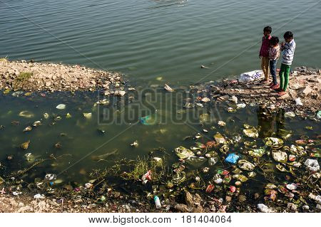 Children Playing Near Dirty Littered With Debris Of The Lake, Watching The Fish.