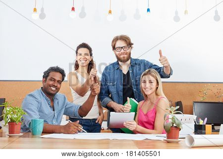 Thumbs up and successful startup team in their office