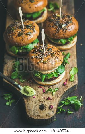 Healthy vegan burger with beetroot and quinoa patty, arugula, avocado sauce and wholegrain buns on rustic wooden board over dark background, selective focus. Clean eating, dieting, detox food concept