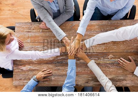 business, teamwork, gesture and corporate concept - group of people sitting at office table and holding hands