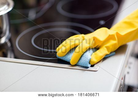 people, housework and housekeeping concept - hand in rubber glove with rag cleaning cooker at home kitchen