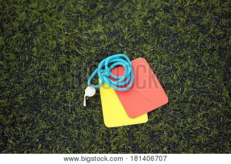 sport, soccer and game - referee whistle and caution cards on football field