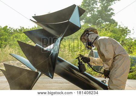 worker painting a machine part impeller in workshop outdoor
