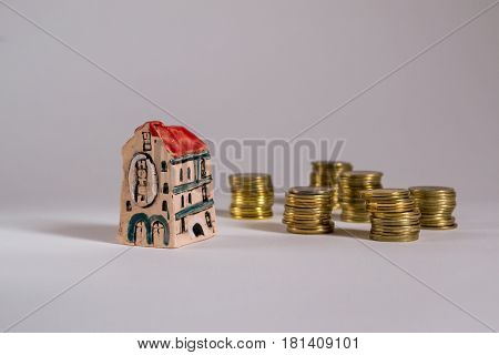 Business concept. Model of hotel with coins on white background