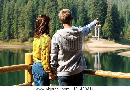 Young beautiful couple holding hands, enjoying mountains lanscape, standing near lake. Copy space.