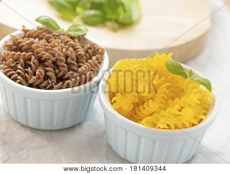 Organic brown rice and corn gluten free pasta in small dishesclose up shot with a selective focus background blurred to add text or copy space