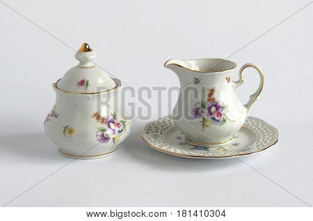 Vintage porcelain creamer and sugar bowl on white background