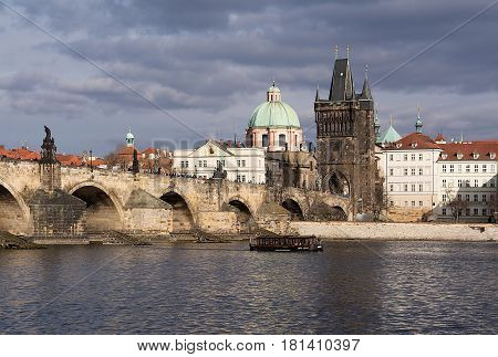 The Charles Bridge with many visitors the Old Town Bridge Tower and a little boat on the river Vltava during a nice day