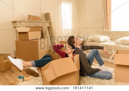 Tired Couple Sitting In Cardbox And On Floor At New Home