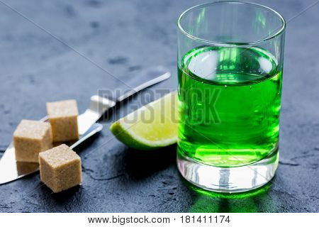 absinthe shots with fresh green lime slices and sugar cubes on dark bar table background