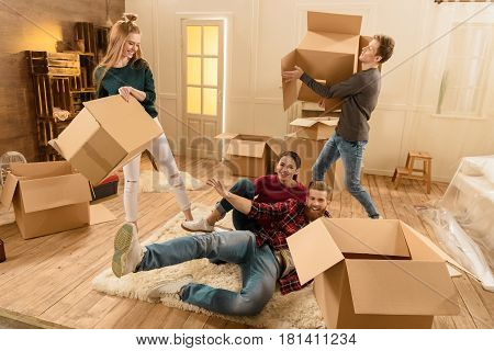friends having fun in new house while unpacking things
