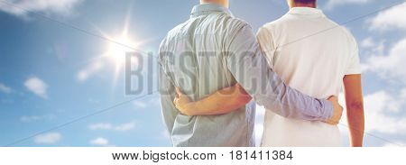 people, homosexuality, same-sex marriage, gay and love concept - close up of happy male gay couple hugging from back over sky and sun background