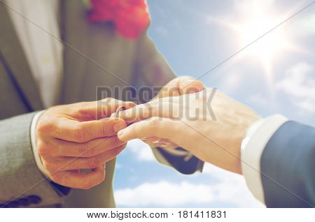 people, homosexuality, same-sex marriage and love concept - close up of happy male gay couple hands putting wedding ring on over sky and sun background