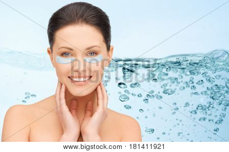 beauty, cosmetology, hydration, people and rejuvenation concept - beautiful young woman face with hydrogel under-eye patches over blue background and water bubbles