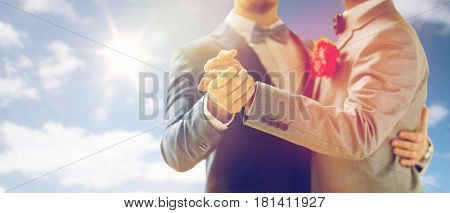 people, homosexuality, same-sex marriage and love concept - close up of happy male gay couple holding hands and dancing on wedding over sky and sun background